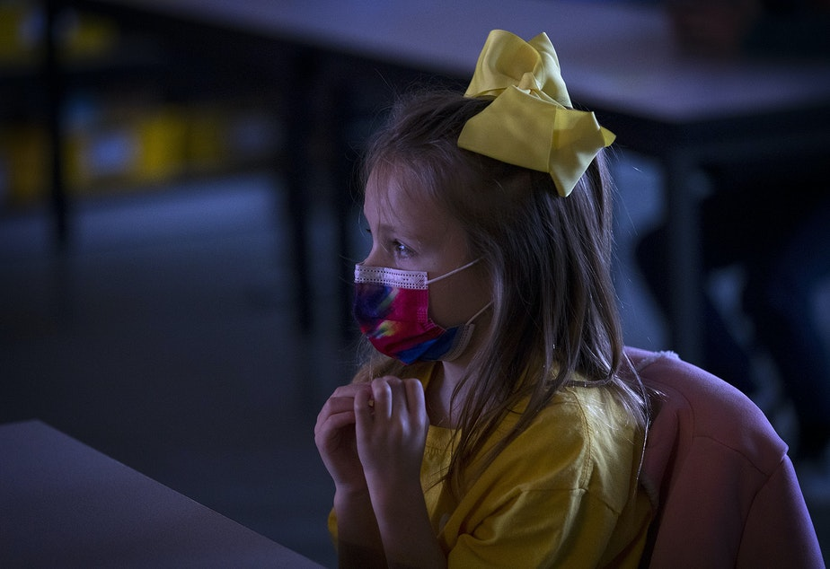caption: Second grade student Camille watches a video about social distancing and other safety precautions in Ms. Gagne's classroom on Thursday, January 21, 2021, as second-grade students returned to in-person learning at Somerset Elementary School in Bellevue.
