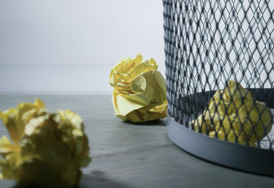 caption: Crumpled papers sit next to an office trash can.
