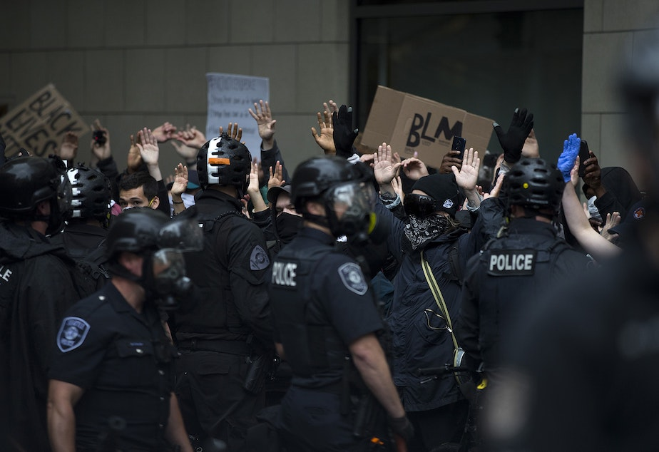 caption: Protesters are shown raising their hands in the air while chanting, 'hands up, don't shoot,' toward Seattle police officers on Saturday, May 30, 2020, near the intersection of 5th and Pine Streets in Seattle. Thousands gathered in a protest following the violent police killing of George Floyd, a Black man who was killed by a white police officer who held his knee on Floyd's neck for 8 minutes and 46 seconds, as he repeatedly said, 'I can't breathe,' in Minneapolis on Memorial Day.