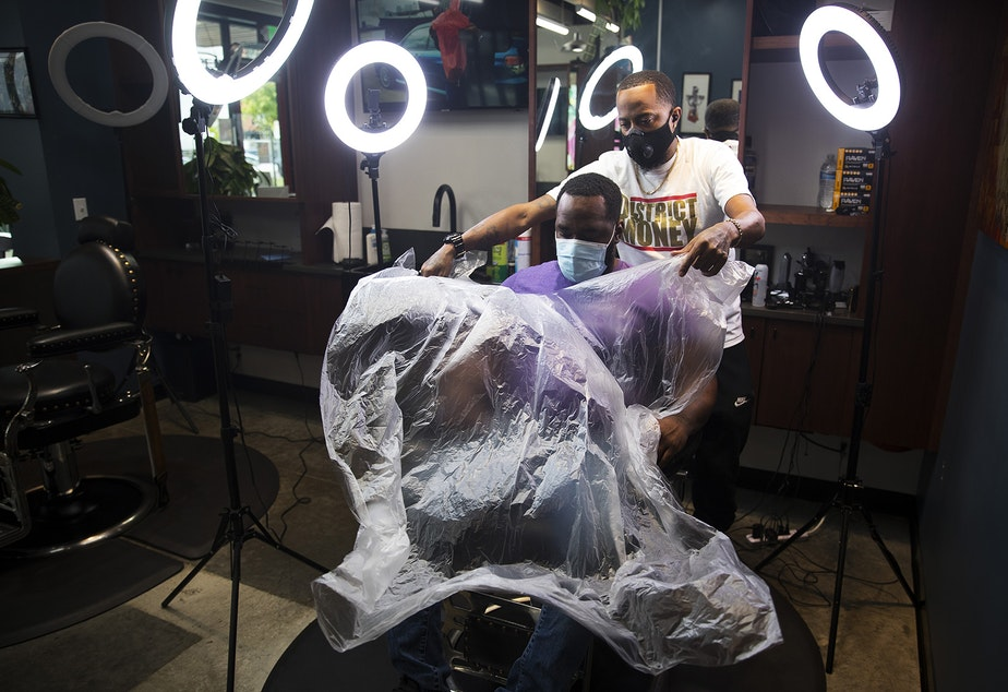 "caption: Barber Jasen Moore gets ready to cut Terrence Brown's hair at Earl's Cuts and Styles Barbershop on October, 15, 2020, in Seattle. ""At first it was a lot of anxiety,"" said Moore, who has been a barber for six years. ""There's a little fear of the unknown. I think that moving forward, the Covid pandemic has allowed us to step back and really see how we can get better as a business for the community to make everybody feel safe and comfortable while they're at Earl's Cuts and Styles."""