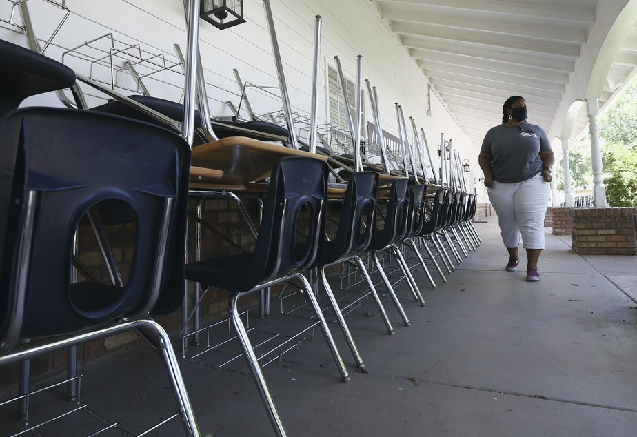 caption: Kristina Washington, special education staff member at Desert Heights Preparatory Academy, walks past desks and chairs at the closed Glendale, Ariz., school in early June.