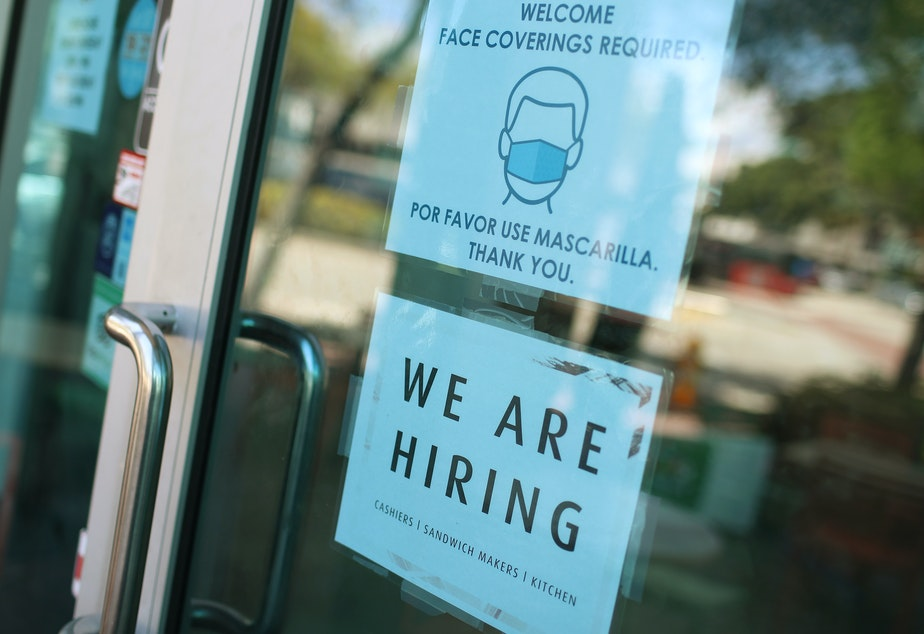 """caption: A store in Miami displays a """"We are hiring"""" sign on March 5. U.S. employers added 916,000 jobs in March, the biggest number since August, amid an improving pandemic outlook and trillions of dollars in stimulus passed by Congress."""