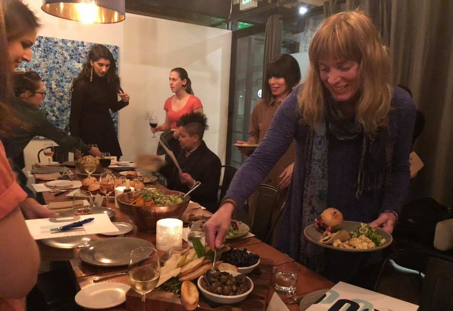 Jennifer Hegeman (foreground) scooping up olives at The Cloud Room in Seattle during KUOW's first Curiosity Club dinner on January 17, 2019.