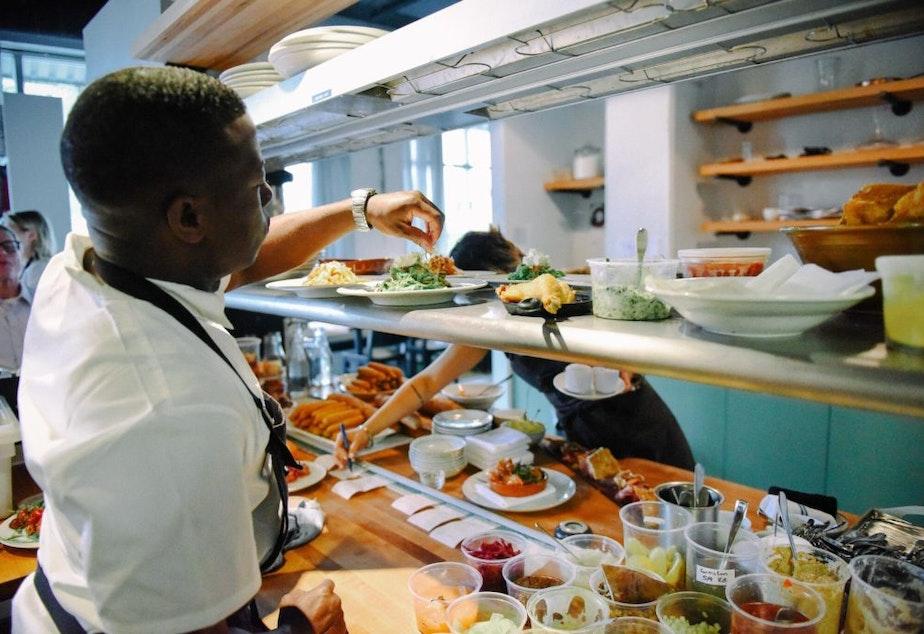 caption: James Beard Award-winnng Chef Edouardo Jordan adds garnish to a dish at Salare in Seattle.
