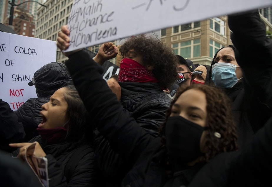 caption: Protesters chant toward Seattle Police officers on Saturday, May 30, 2020, in Seattle. Thousands gathered in a protest that turned violent following the police killing of George Floyd, a black man who was killed by a white police officer who held his knee on Floyd's neck for 8 minutes and 46 seconds, as he repeatedly said, 'I can't breathe,' in Minneapolis on Memorial Day.