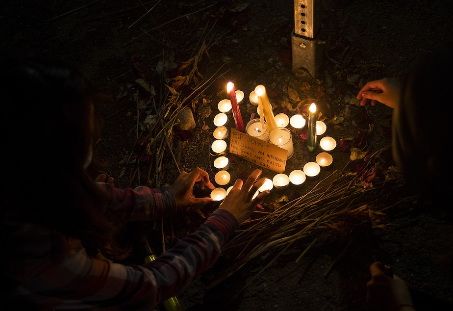 caption: Members of the Everyday March light candles and place them in the shape of a heart to honor John T. Williams, a First Nations wood carver who was shot and killed by Seattle Police in 2010, on Tuesday, August 4, 2020, near the home of Seattle City Councilmember Debora Juarez in Seattle.
