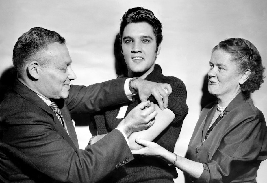 caption: Elvis Presley got his polio vaccination from Dr. Harold Fuerst and Dr. Leona Baumgartner at CBS' Studio 50 in New York City on Oct. 28, 1956. The chart-topping singer took part in a March of Dimes campaign to convince teens to get vaccinated.