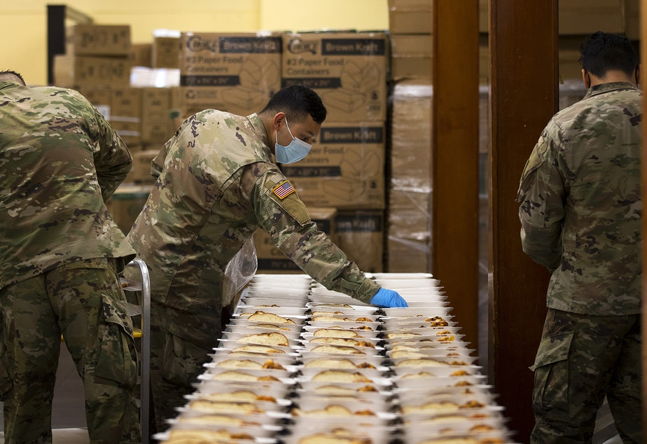 caption: Spc. David Penalba with the U.S. Army National Guard works to prepare daily meals for people experiencing homelessness ahead of the Thanksgiving holiday, on Tuesday, November 24, 2020, in Seattle.