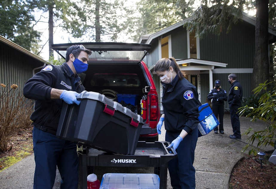 caption: Bellevue firefighters Ryan Armstrong, left, and Alexa Dillhoff, right load supplies into a vehicle after vaccinating residents of the Optimus Family Home against Covid-19 on Friday, February 5, 2021, in Bellevue.