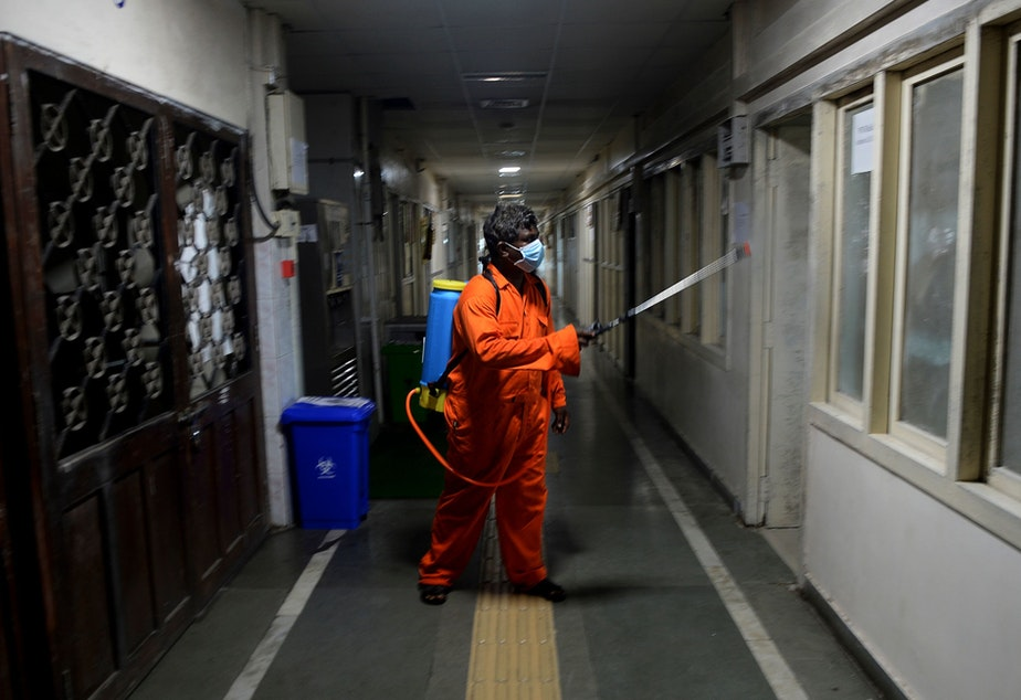 caption: A health worker sprays disinfectant inside government offices as a preventive measure against the COVID-19 coronavirus.