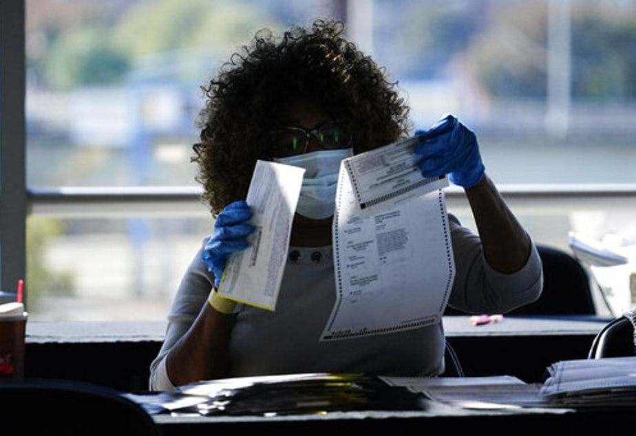 caption: An election personnel examines a ballot as vote counting in the general election continues at State Farm Arena, Wednesday, Nov. 4, 2020, in Atlanta.