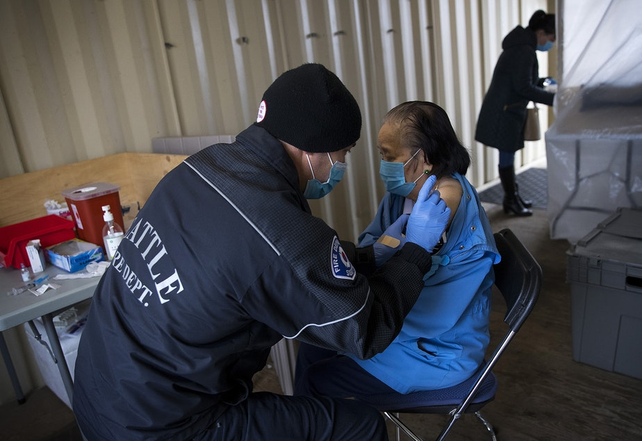 caption: Seattle Firefighter and EMT Dave Pedras, left, administers the first dose of the Moderna Covid-19 vaccine for Du, 87, on Thursday, February 18, 2021, at the West Seattle Covid-19 testing site on Southwest Thistle Street in Seattle. The pop-up vaccination clinic was set up for older Latino community members who were referred by El Comite or Villa Comunitaria.