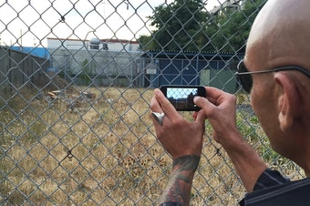 A Ballard man snaps a photo of a vacant lot that may one day host a tent city for the homeless.