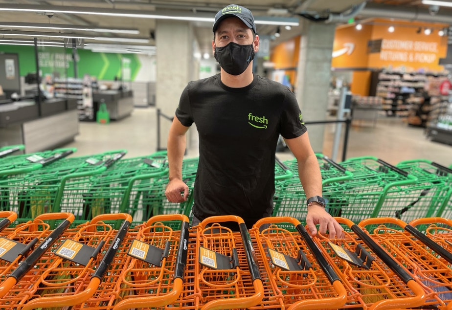 """caption: Dany Curbelo poses among some of the older style shopping carts at Amazon Fresh for customers who don't want to use the smart """"Dash"""" carts"""