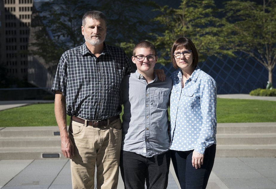 caption: From left, Mark, Paxton and Cheryl Enstad pose for a portrait on Thursday, October 5, 2017, outside of the ACLU of Washington on 9th Ave., in Seattle.