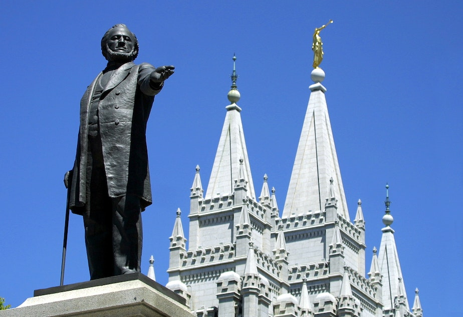 caption:  A statue of Brigham Young, second president of the Church of Jesus Christ of Latter Day Saints stands in the center of Salt Lake City with the Mormon Temple spires in the background 19 July 2001. (George Frey/AFP via Getty Images)