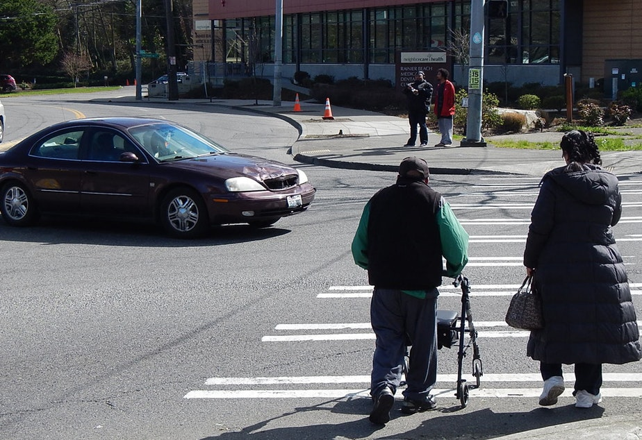 Cars and pedestrians compete for space in a busy Rainier Valley crosswalk.