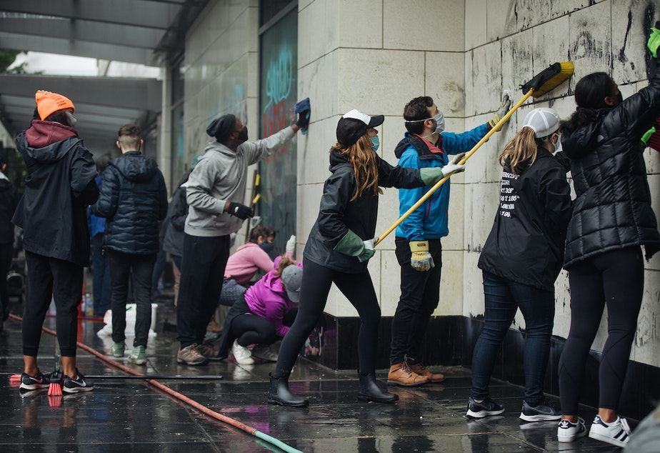 caption: People descended on downtown Seattle on Sunday morning to scrub down the city after a day and night of protests against racism. The protests for were George Floyd, a Black man who died at the hands of police in Minneapolis.