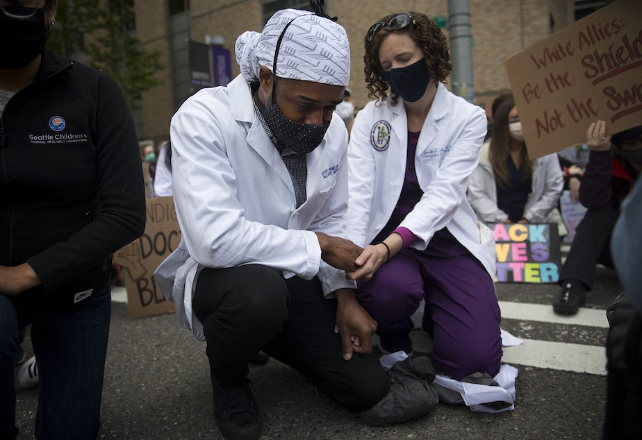 caption: A tear falls from Dr. Hayden Hamilton's eye while kneeling with Dr. Jennifer Hamilton, right, during a moment of silence on Saturday, June 6, 2020, outside of Harborview Medical Center in Seattle. Healthcare workers gathered in a march to Seattle City Hall in protest to demand justice and an end to police violence.