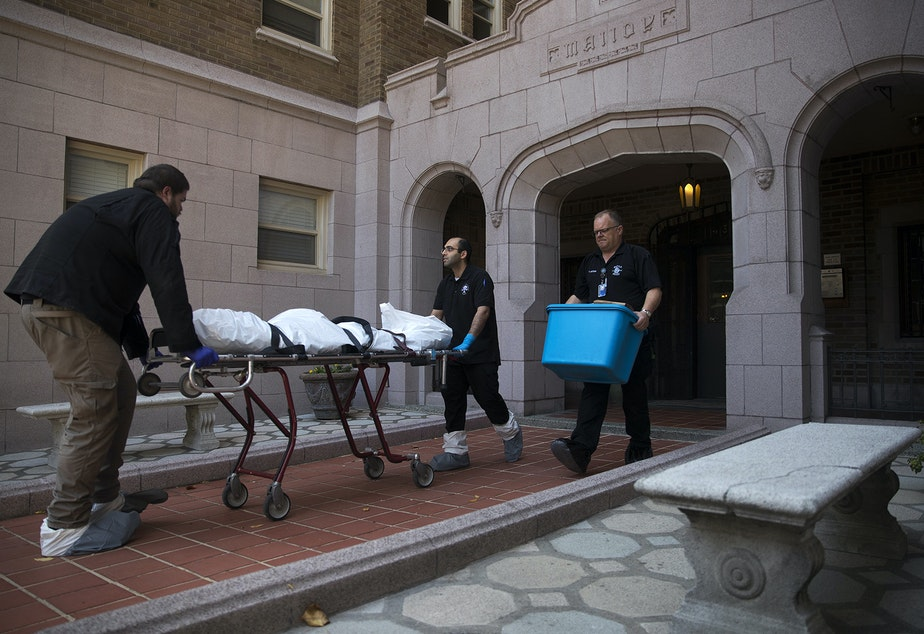 caption: A body is removed from an apartment on Monday, September 4, 2018, at the Malloy Apartments near the intersection of Northeast 43rd Street and 15th Avenue Northeast in Seattle.
