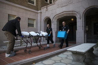 A body is removed from an apartment on Monday, September 4, 2018, at the Malloy Apartments near the intersection of Northeast 43rd Street and 15th Avenue Northeast in Seattle.