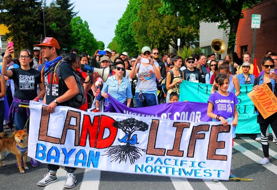 People walk in the May Day labor march in Seattle on Friday.
