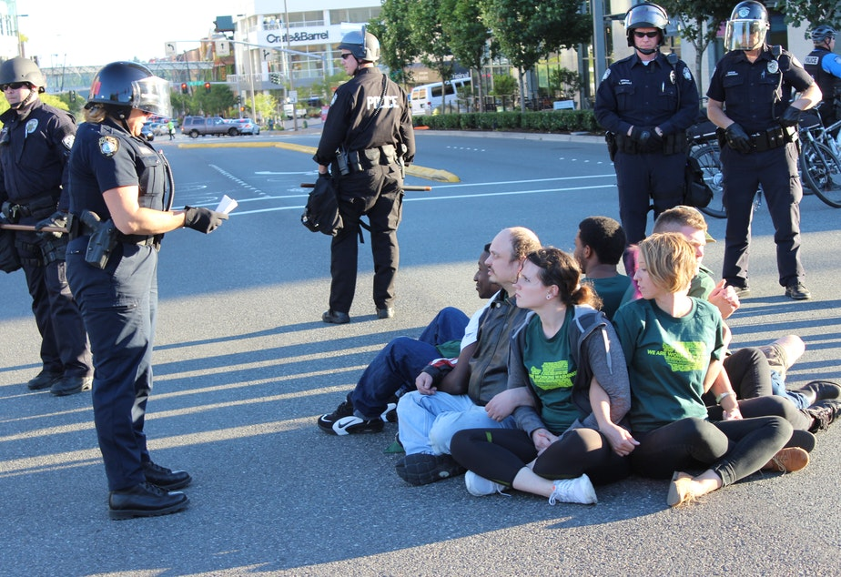 caption: Bellevue police prepare to arrest eight minimum wage activists blocking a downtown intersection.