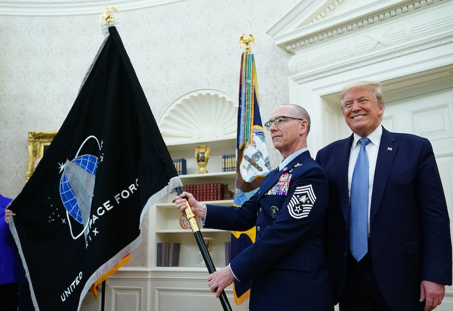 caption: U.S. Space Force Senior Enlisted Advisor CMSgt Roger Towberman, standing with President Trump, presents the Space Force Flag in the Oval Office on March 15.