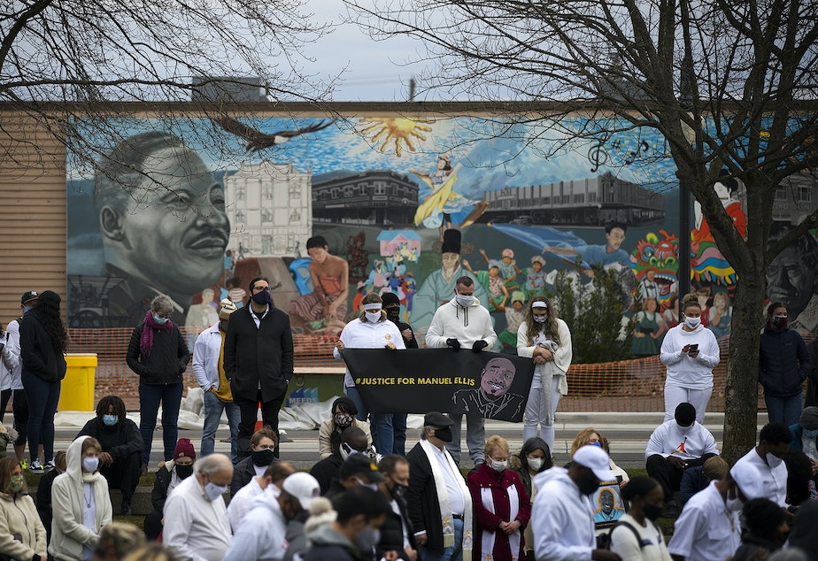 """caption: A crowd gathers at People's Park on Sunday, February 28, 2021, following a silent march ahead of the one-year mark of the Tacoma police killing of 33-year-old Manuel Ellis who said, """"I can't breathe, sir,"""" before he died, on Martin Luther King Jr. Way in Tacoma."""
