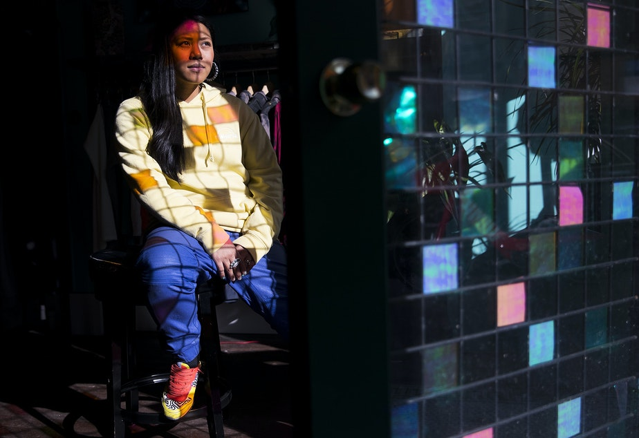 Karleen Ilagan, owner of Moksha, poses for a portrait in the light shining through a colorful grill that was put in place to deter burglars at the store on Thursday, February 21, 2019, in Seattle.