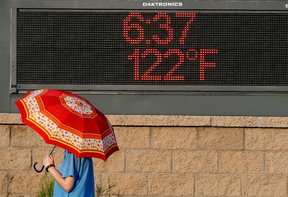 caption: A pedestrian uses an umbrella to get some relief from the sun as she walks past a sign displaying the temperature on June 20, 2017 in Phoenix, Ariz.
