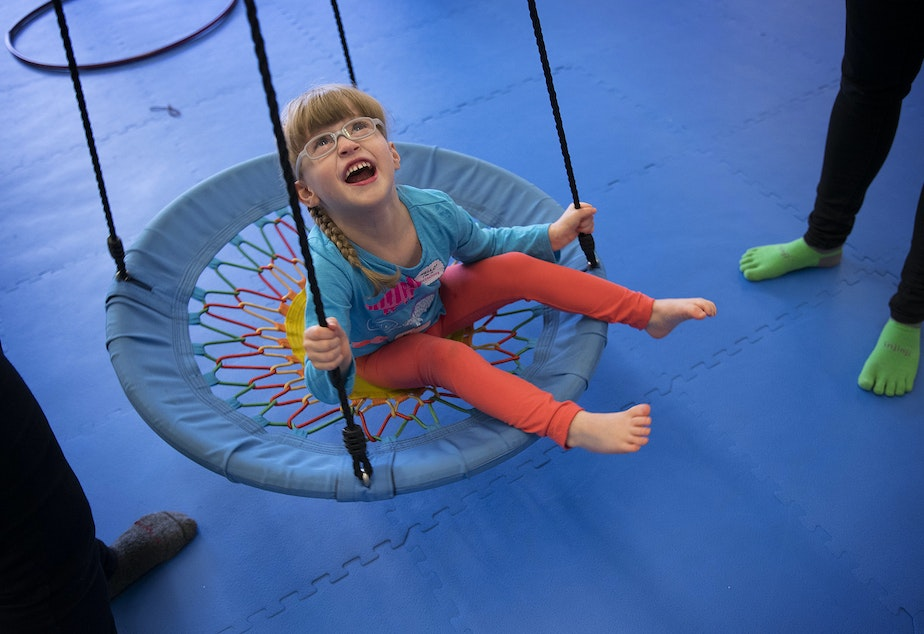 Lillian Rockett, 4, laughs as she is pushed on a circular swing on Sunday, October 1, 2017, at We Rock the Spectrum Kid's Gym in Bellevue.