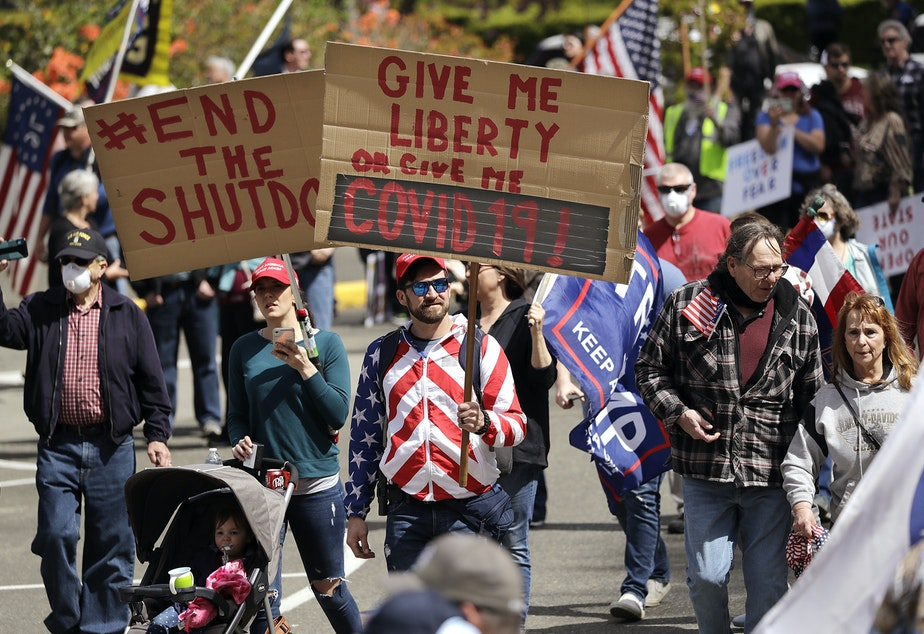 """caption: Demonstrators begin to gather at a protest opposing Washington state's stay-home order to slow the coronavirus outbreak Sunday, April 19, 2020, in Olympia, Wash. Washington Gov. Jay Inslee has blasted President Donald Trump's calls to """"liberate"""" parts of the country from stay-at-home and other orders that are designed to combat the spread of the coronavirus. Inslee says that Trump is fomenting a potentially deadly """"insubordination"""" among his followers before the pandemic is contained."""