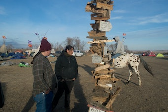 A man rides a horse past a post with signs pointing in all directions, towards the homelands of the thousands of indegnous people who came to Standing Rock. Native people lived there in a way they haven't for hundreds of years.