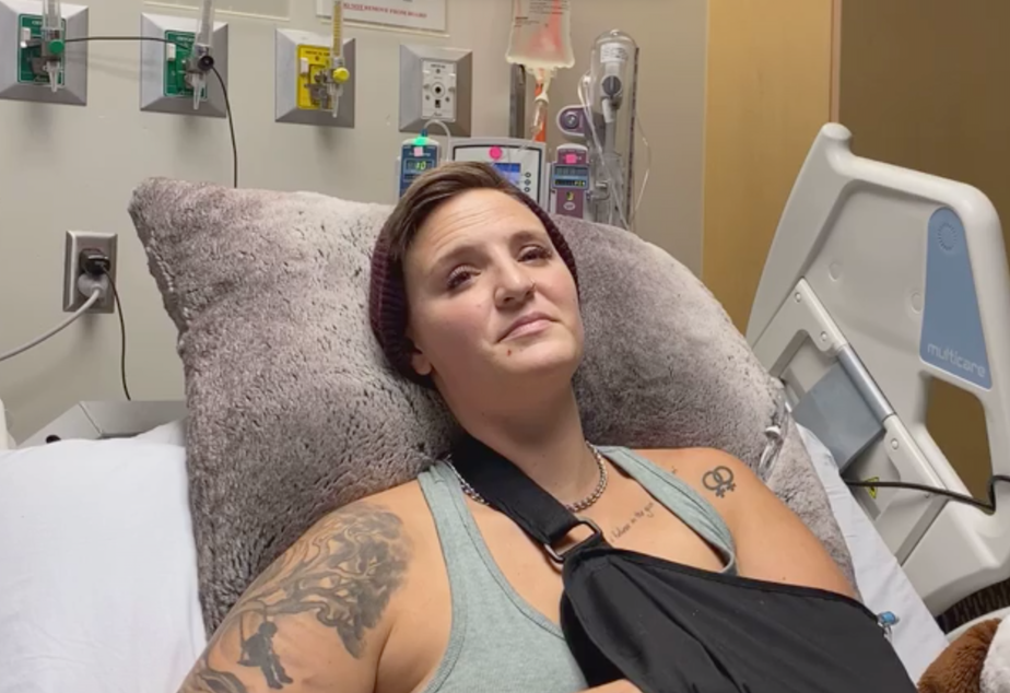 caption: Protester Diaz Love, 32, sits in their hospital bed at Harborview Medical Center on Wednesday, July 22 recovering from multiple injuries. Diaz and another protester, Summer Taylor, were struck by driver Dawit Kelete in the early morning hours of July 4 amid a demonstration against racism and police brutality on Interstate 5.