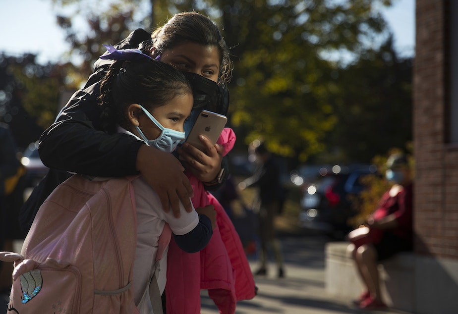 caption: Ariana Perez hugs her niece, Romina Ruiz, 6, before her first day of first grade at Mount View Elementary school on Thursday, September 2, 2021, in Seattle.