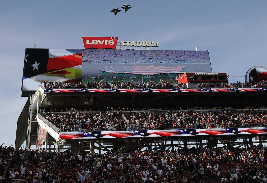 caption: Military planes fly over Levi's Stadium on Thursday during the playing of the national anthem. A cheerleader took a knee during the pre-game anthem, and may be the first NFL cheerleader to do so.