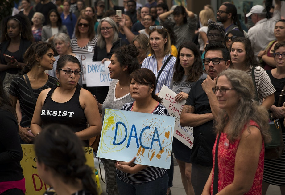 caption: A crowd gathers during a community rally in support of DACA recipients on Tuesday, September 5, 2017, at El Centro De La Raza in Seattle.