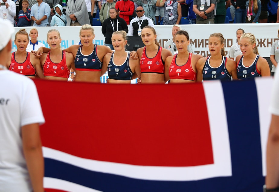 caption: The Norwegian women's beach handball team is being fined for wearing shorts during a recent tournament game. The team is seen here after a game in 2018.