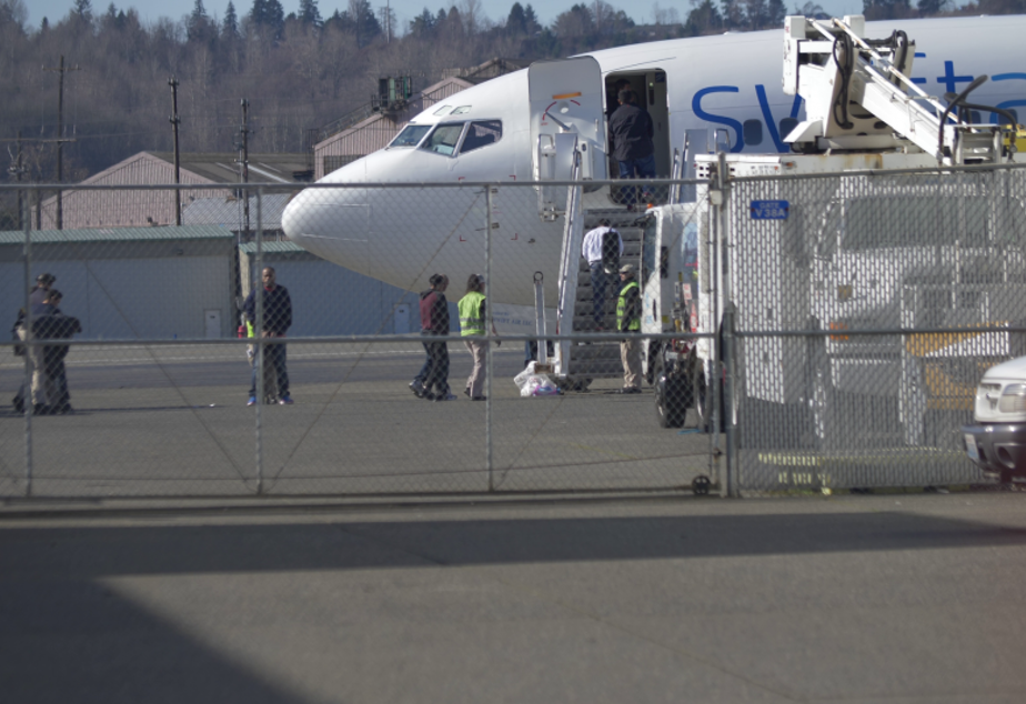 caption: In this still image from a vide, detainees are loaded onto a Swift Air charter flight at King County International Airport (Boeing Field) in Seattle, WA for a February 26 ICE Air flight under callsign RPN 529.