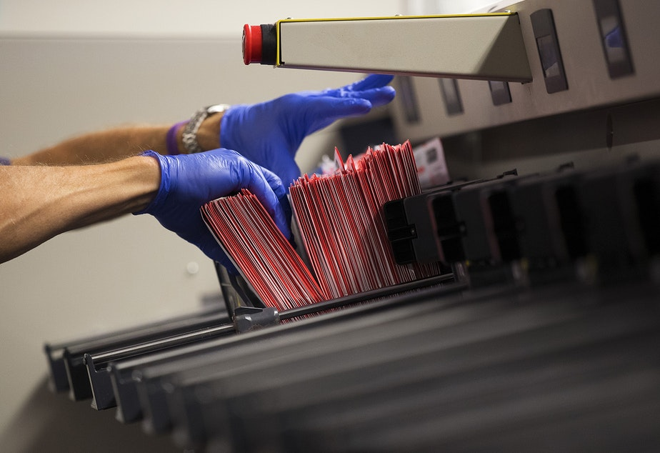 caption: An elections worker removes ballots from a ballot sorting machine on Wednesday, October 28, 2020, at King County Elections in Renton.