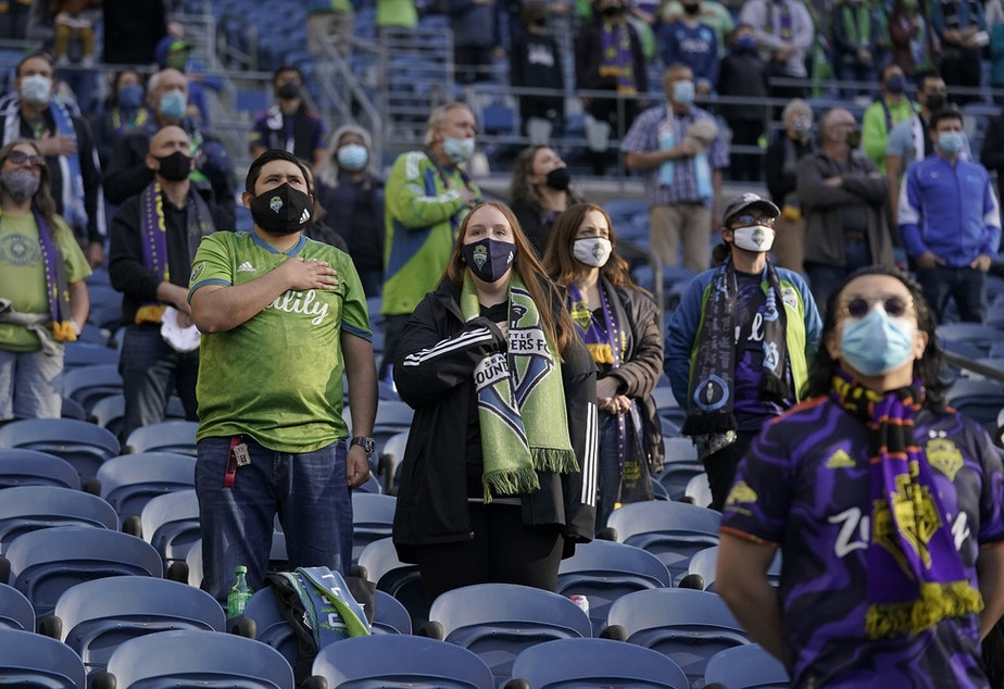 caption: Seattle Sounders fans wear masks as they stand during the singing of the national anthem before an MLS soccer match against the Los Angeles Galaxy, Sunday, May 2, 2021, in Seattle.