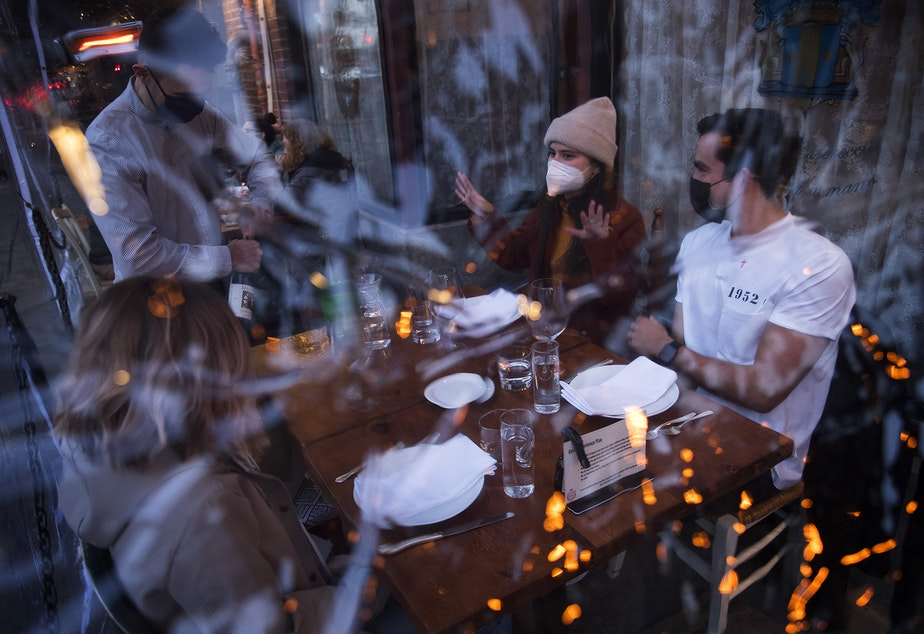 caption: Server Luis Velez opens a bottle of wine for customers Mary Graf, left, Sophie Mandel and Andy Peraza, right, shown through a sheet of plastic surrounding the table, on Wednesday, October 21 , 2020, at Spinasse on Capitol Hill in Seattle.
