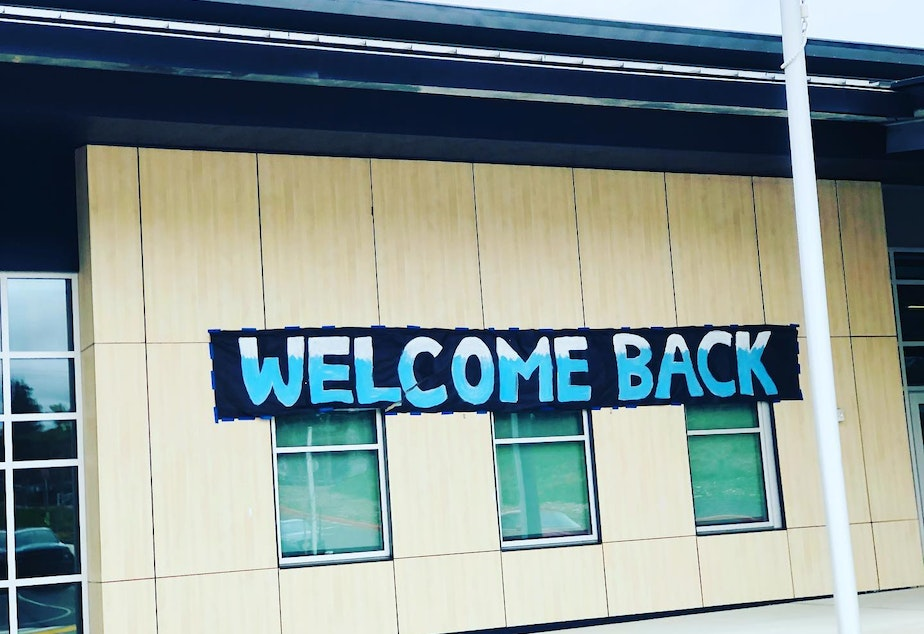 caption: A sign welcomes students back to Glacier Middle School in SeaTac in April 2021, after months of remote learning during the Covid-19 pandemic.