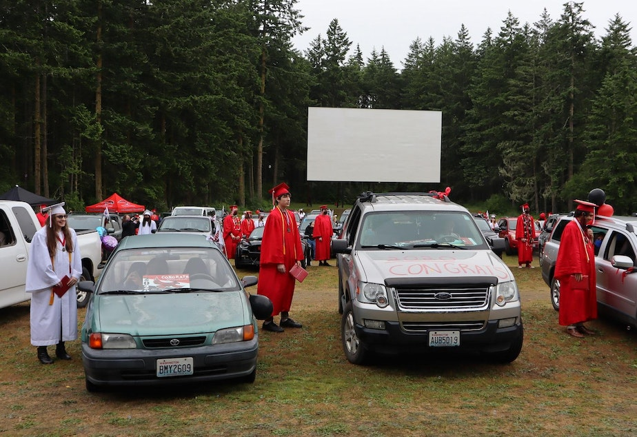 caption: Port Townsend High School seniors looked to a temporary stage near the back of the drive-in theater, rather than toward the big screen, during their graduation on June 12, 2020.