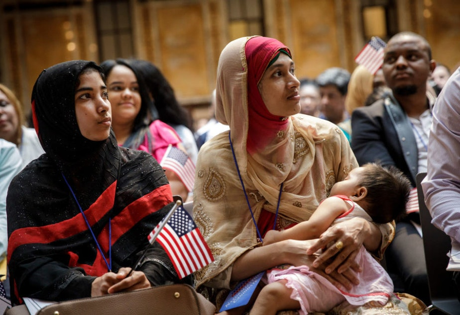 caption: Mosammat Rasheda Akter, originally from Bangladesh, holds her 7 month-old daughter Fahmida as she waits to officially become a U.S. Citizen during a naturalization ceremony at the New York Public Library, July 3, 2018 in New York City. (Drew Angerer/Getty Images)