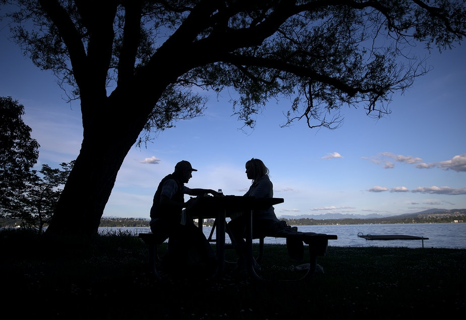caption: Lee Markholt, left, and Tara Conklin, right, have a picnic on Friday, May 15, 2020, at Madrona Park in Seattle.