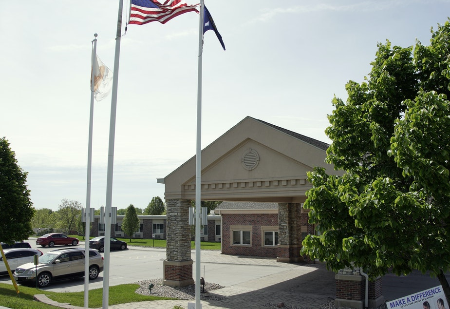 caption: A flag flies on the grounds of the Life Care Center nursing and rehabilitation facility in Elkhorn, Neb., where a large number of staff and residents tested positive for COVID-19.
