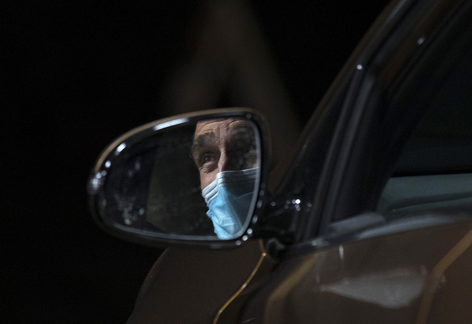 caption: Dennis Haack, a family medicine physician at Neighborcare Health, is shown through a side mirror talking with a healthcare worker while waiting for 15 minutes after receiving his first dose of the Moderna Covid-19 vaccine on Thursday, January 7, 2021, at a drive-thru vaccine clinic for healthcare workers in Renton.