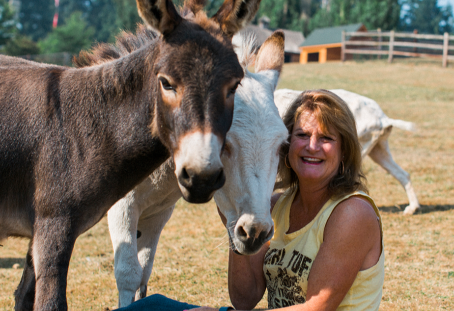 Diane Gockel poses with some donkeys at the Sammamish Animal Sanctuary.
